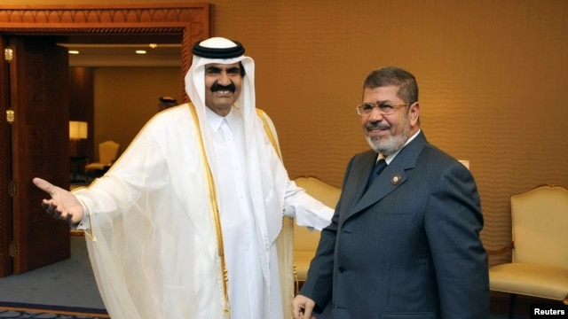 Qatar's Emir Sheikh Hamad bin Khalifa al-Thani (L) greets Egypt's President Mohamed Mursi during the Arab League summit in Doha, March 26, 2013.