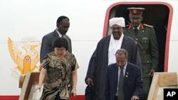 ARCHIVES - Le président soudanais Omar el-Béchir, turban blanc sur la tête, descend d'un avion.