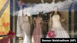 FILE - Mannequins in wedding gowns are seen in a window display on March 15, 2021, at a bridal store in Nogales, Ariz., that has been closed for nearly a year because of the pandemic.AP Photo/Suman Naishadham, File)