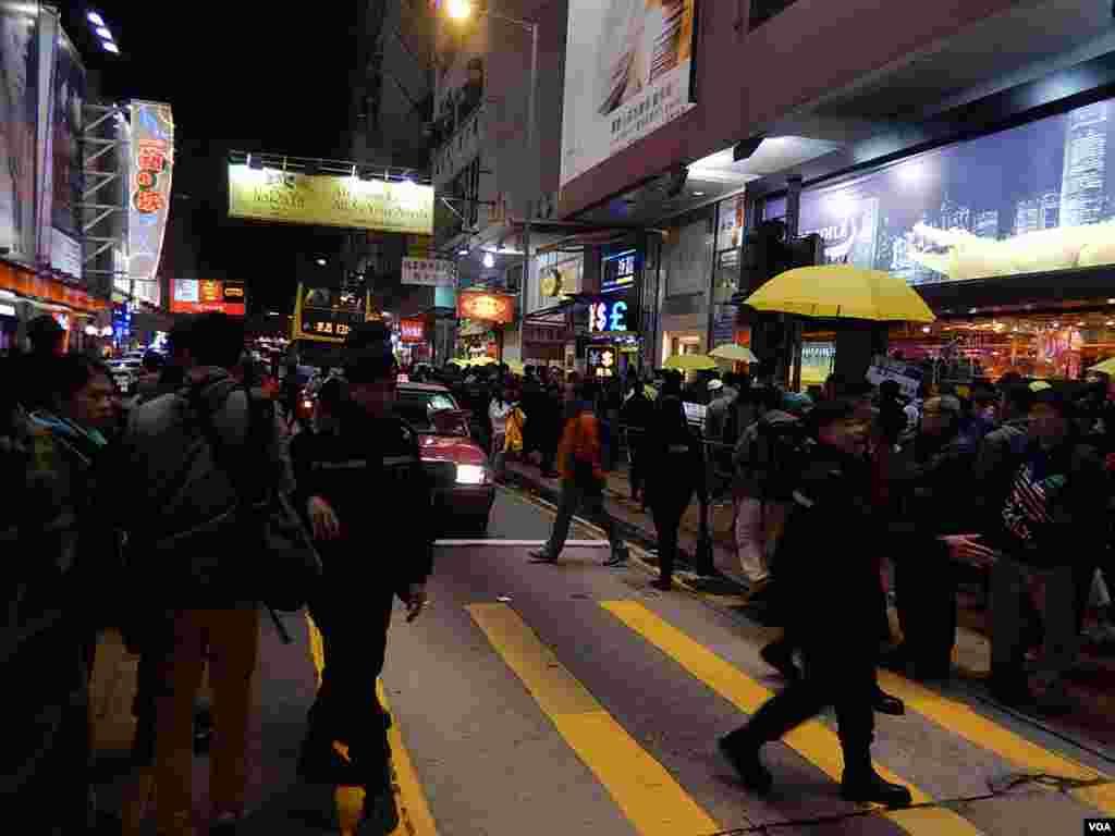 警員驅趕站在馬路上的「購物團」人士站回行人路上