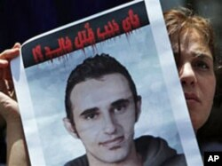 """An activist carries a picture of slain Khaled Said with Arabic that reads """"Why was Khaled killed?"""" during a protest at the Egyptian Journalists Syndicate in Cairo, June 19, 2010"""