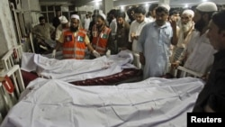 Police and hospital staff stand next to bodies of victims of a bomb attack, at the Lady Reading Hospital in Peshawar, August 31, 2012.