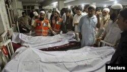 Polisi dan petugas rumah sakit berdiri dekat jenazah korban bom mobil di Peshawar, Pakistan. (Foto: Reuters)
