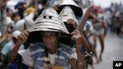 Wearing their traditional warrior helmets and jewelry, Tao aboriginal elders arrive at a traditional fishing boat launching ceremony in a village on Orchid Island, Taiwan.