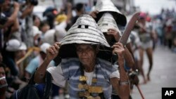 FILE - Wearing their traditional warrior helmets and jewelry, Tao aboriginal elders arrive at a traditional fishing boat launching ceremony in a village on Orchid Island, Taiwan.