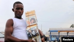 A boy sells a music CD along a road in NIgeria's city of Port-Harcourt.