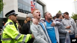 People heckle the Mayor of London, Boris Johnson, not pictured, as he leave the scene of a terror attack in Woolwich, southeast London, May 23, 2013.