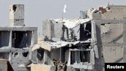 敘利亞民主力量的武裝人員在拉卡升起旗幟
