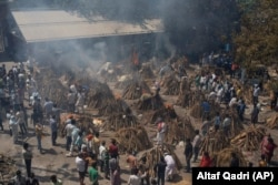 Multiple funeral pyres of those who died of COVID-19 burn at a ground that has been converted into a crematorium for the mass cremation of coronavirus victims, in New Delhi, India, Saturday, April 24, 2021.