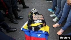 یک معترض خود را به شکل مرده ای در آورده که روی آن نوشته شده «گلوله نه، غذا آری»