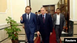 Iraq's new Defense Minister Khaled al-Obeidi (C) walks with acting Defense Minister Saadoun al-Dulaimi (L) at the Defense Ministry in Baghdad, Oct. 19, 2014.
