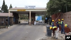 Builders work outside the main entrance of the Weskoppies Psychiatric Hospital, in Pretoria, South Africa, May 20, 2014.