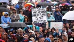 """A person hold up a sign that reads """"Fund Climate Change Research Saving The Planet Is Not a Waste of Money"""" during the March for Science in Washington, D.C., April 22, 2017."""