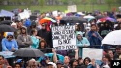 "Seorang peserta pawai ""March for Science"" di Washington DC, 22 April 2017, membawa kertas bertuliskan pesan dalam bahasa Inggris yang artinya ""Anggaran untuk Riset terkait Perubahan Iklim (adalah) untuk Menyelamatkan Dunia, Bukan Pemborosan."" (AP Photo/Sait Serkan Gurbuz)."