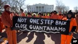 Demonstran yang mengenakan pakaian seperti tahanan penjara Guantanamo memegang poster bertuliskan tuntutan penutupan Guantanamo di Kuba saat berunjuk rasa di Gedung Putih di Washington, 11 Januari 2016.