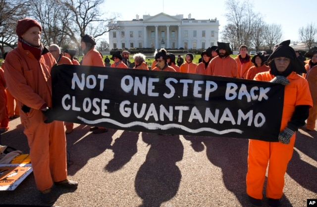Protesters depicting Guantanamo Bay detainees hold signs calling for closing the Guantanamo Bay detention center in Cuba, at a rally at the White House in Washington, Jan. 11, 2016.