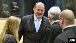 Former Bosnian Serb interior minister Mico Stanisic (C) greets his lawyers as he arrives on March 27, 2013 to attend the Trial Chamber Judgement at the International Criminal Tribunal for the former Yugoslavia in The Hague, The Netherlands.