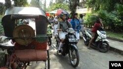 Pelajar bermotor melintas di jalur lambat Jl. Adisucipto, Solo. (VOA/Yudha Satriawan)