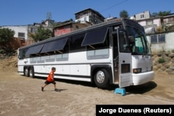 A migrant child runs towards a bus converted in a classroom as part of Schools On Wheels program by California's 'Yes We Can' organization, in Tijuana, Mexico August 2, 2019