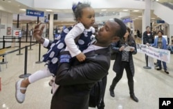 Abdisellam Hassen Ahmed, a Somali refugee who had been stuck in limbo after President Donald Trump temporarily banned refugee entries, holds his 2-year-old daughter, Taslim, after meeting her for the first time upon arriving at Salt Lake International Airport in Salt Lake City, Utah, Feb. 10, 2017.