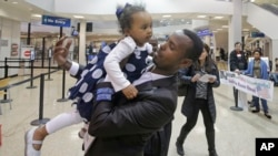 Abdisellam Hassen Ahmed, pengungsi Somalia yang nasibnya sempat tidak jelas menyusul instruksi Presiden AS Donald Trump, menggendong putrinya setelah bertemu lagi di Bandar Udara Internasional Salt Lake City, Utah (10/2). (AP/Rick Bowmer)