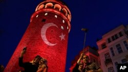 People take photos at the iconic Galata Tower, illuminated in Turkish flag colors, in Istanbul, July 30, 2016. Dozens of staff at Turkey's highest court have been suspended from their jobs as part of the crackdown in the wake of a failed military coup, au