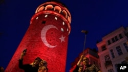 People take photos at the iconic Galata Tower, illuminated in Turkish flag colors, in Istanbul, July 30, 2016. Some signals from President Recep Tayyip Erdogan's administration show no letup in reprisals following an abortive coup attempt two weeks ago.