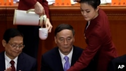 Vice Premier Wang Qishan, center, is served a drink by a hostess during the opening session of the 18th Communist Party Congress at the Great Hall of the People in Beijing, Nov. 8, 2012