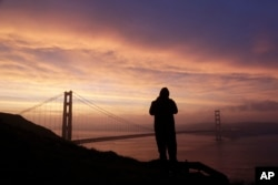 Jeunne Victorino, visiting from San Diego, photographs the sunrise and the Golden Gate Bridge from the Marin Headlands Tuesday, Jan. 17, 2017, in San Francisco. (AP Photo/Marcio Jose Sanchez)
