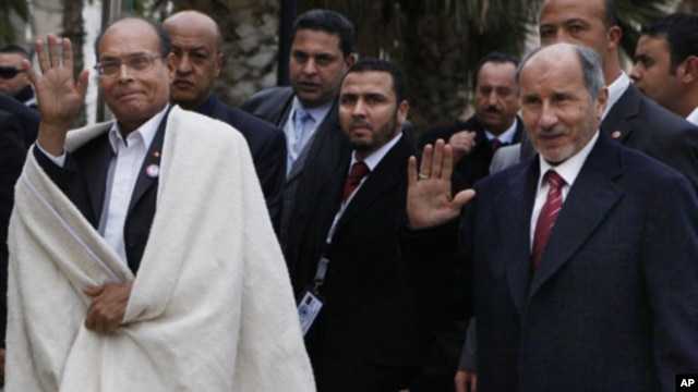 Tunisia's new president Moncef Marzouki, left, is accompanied by Libyan Transitional National Council chairman Mustafa Abdul-Jalil after his arrival in Tripoli, Libya, Monday, Jan. 2, 2012.