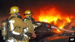 Firefighters battle an arson car fire in Los Angeles , Jan. 2, 2012.