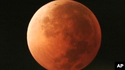FILE - In this Aug. 28, 2007 photo, the moon takes on different orange tones during a lunar eclipse seen from Mexico City. On Jan. 31, 2018, a supermoon, blue moon and a lunar eclipse will coincide for first time since 1982 and will not occur agai