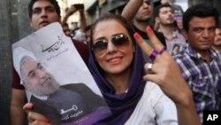 Tahran'da seçim sonrası zafer işareti yapan İran'ın yeni cumhurbaşkanı Hasan Ruhani'nin bir kadın destekçisi