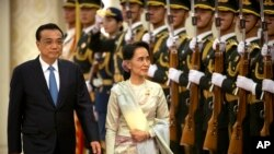China's Premier Li Keqiang (L) and Myanmar State Counselor and Foreign Minister Aung San Suu Kyi review an honor guard during a welcome ceremony at the Great Hall of the People in Beijing, Aug. 18, 2016.