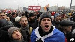 Masu zanga zangar a dandalin Bolotnaya a birnin Moscow. A bayansu kuma alame ce dake kira ga Prime Minista Putin yayi murabus.