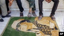 Libyan rebels use a carpet with the image of Moammar Gadhafi as a doormat at their camp, set up in a district of Gadhafi sympathizers in the stronghold city of Tarhouna, 100 kilometers southeast of Tripoli, Libya, August 29, 2011
