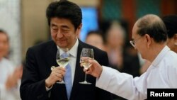 Japan's Prime Minister Shinzo Abe (L) and Burma's President Thein Sein toast during lunch at the Myanmar International Convention Center in Naypyitaw, May 26, 2013.