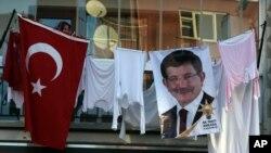 2015年10月31日,安卡拉,一位土耳其女子在阳台上晾晒衣服,聆听土耳其总理达武特奥卢在正义与发展党集会上发表讲话。