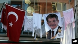 With her clothes hanging to dry on a balcony, a woman listens to Turkish Prime Minister Ahmet Davutoglu during a rally of his Justice and Development Party, or AKP, in Ankara, Oct. 31, 2015.