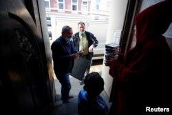 Relawan Turki Goecen Muelayim, 55, (kiri) dan Ural Hasan, 55, dari layanan pengiriman makanan buka puasa, membagikan makanan kepada seorang perempuan Muslim yang membutuhkan dan anaknya selama Ramadan di tengah pandemi COVID-19 di Wupperta, Jerman. (Foto: dok).