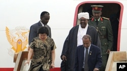 Sudan's leader Omar al-Bashi, center, leaves his aircraft as he arrives at Beijing International Airport, June 28, 2011.