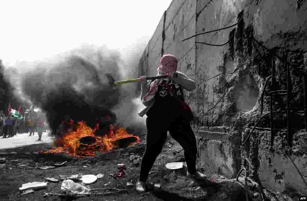 A female Palestinian demonstrater uses an axe to try and destroy a part of the Israeli controvertial separation wall separating the West Bank city of Abu Dis from east Jerusalem, during clashes with Israeli security forces.