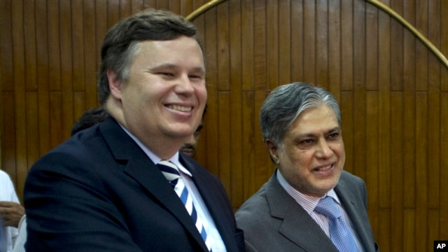 FILE - Pakistani Finance Minister Muhammad Ishaq Dar, right, shakes hands with IMF mission chief Jeffrey Franks after a joint news conference in Islamabad, Pakistan, July 4, 2013.