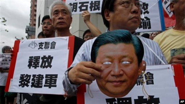 Protester holds mask of Chinese President Xi Jinping during demonstration for Chinese journalist Gao Yu, Hong Kong publisher Yao Wentian, and Chinese lawyer Pu Zhiqiang, Chinese liaison office, Hong Kong, May 11, 2014.