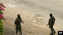 عساکر طرفدار رئیس جمهور باگبو در جادۀ نزدیک قصر ریاست جمهوری گزمه مینمایند.