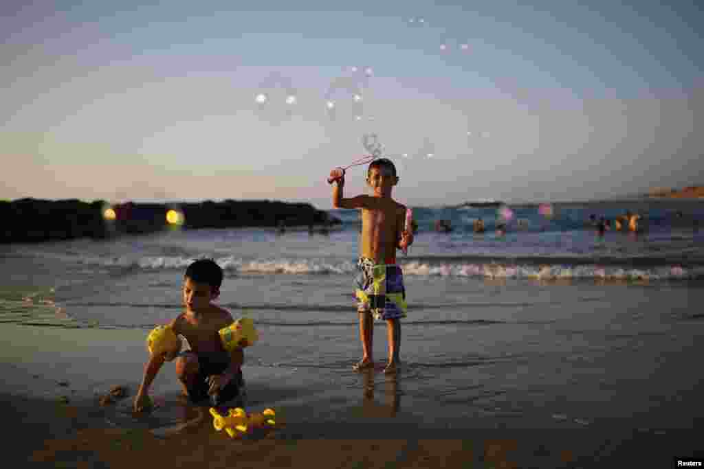 A child blows soap bubbles on the shore of the Mediterranean sea at the southern Israeli city of Ashkelon August 11, 2014.