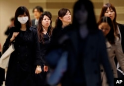 FILE - Female office workers head to their workplace during morning rush hour in Tokyo.