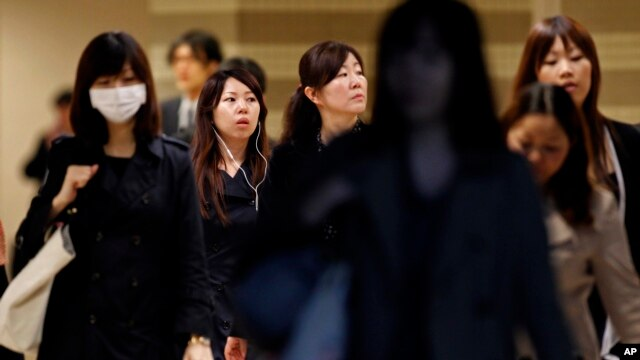 FILE - Female office workers head to their workplace during morning rush hour in Tokyo. Without a substantial increase in the birthrate or loosening of staunch Japanese resistance to immigration, the population is forecast to fall to about 108 million by 2050 and to 87 million by 2060.