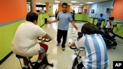 In this 2007 file photo, fitness expert Jose Ortiz helps train overweight boys on stationary bikes in Puerto Rico. (AP Photo/Brennan Linsley)