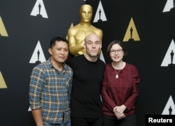 """""""The Look of Silence"""" documentary subject Adi Rukun and filmmakers Joshua Oppenheimer, center, and Signe Byrge Sorensen pose at a reception in Beverly Hills, Calif., Feb. 24, 2016. The film is an Academy Awards contender."""